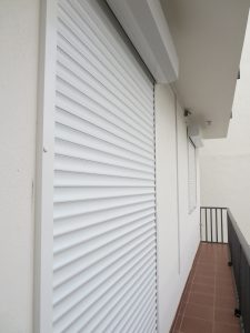 A white shutter system on a balcony.